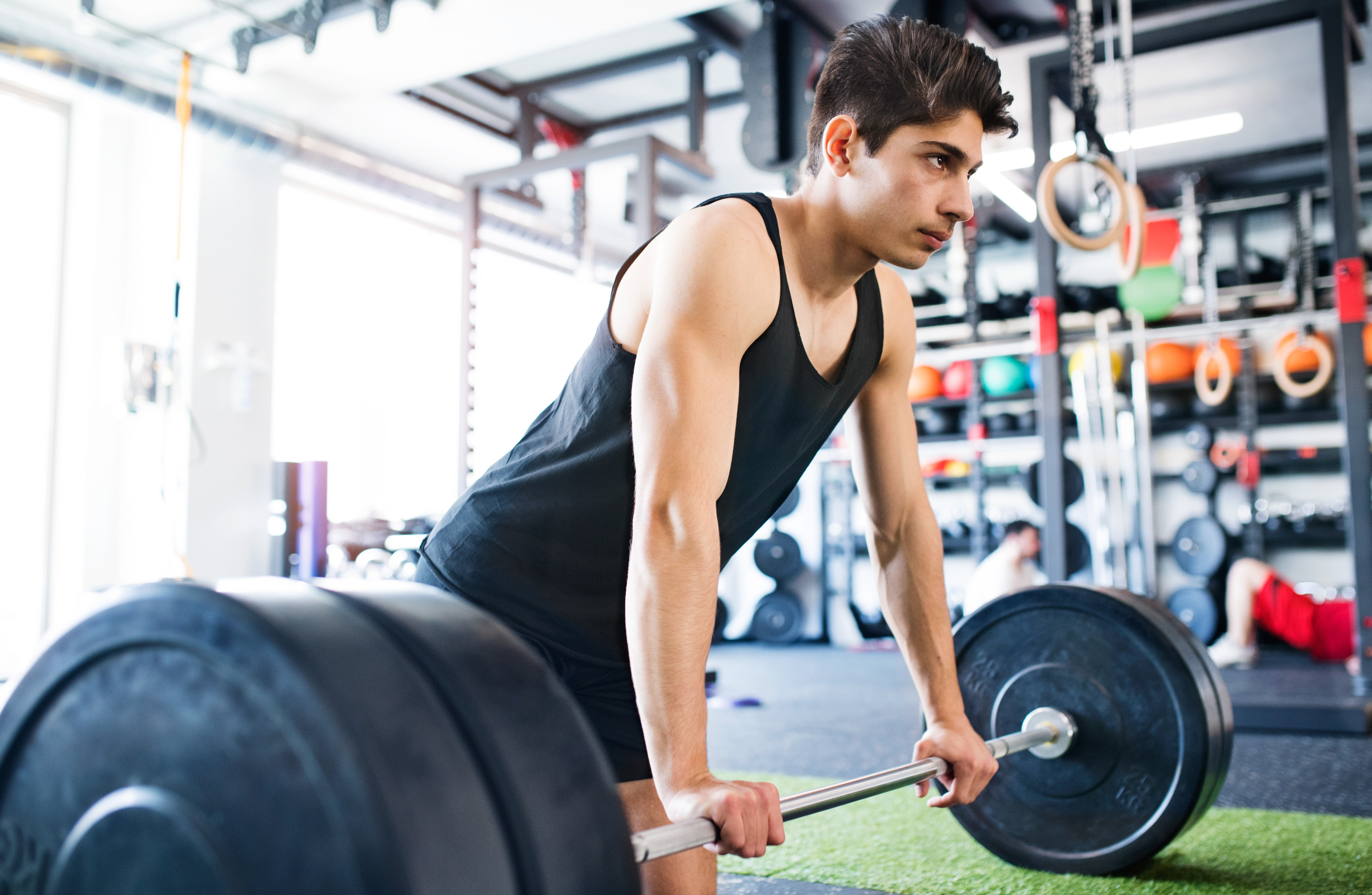 Young fit hispanic man in gym lifting heavy barbell, flexing muscles