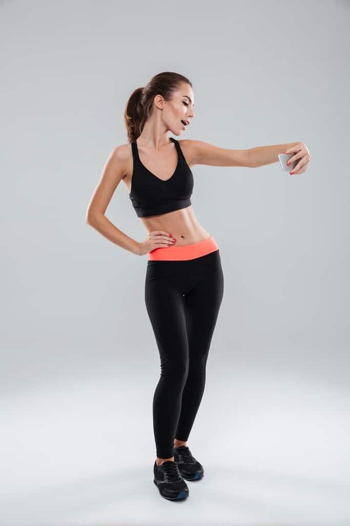 Full length picture of beauty fitness woman posing with arm on hip and making selfie on her smartphone over gray background