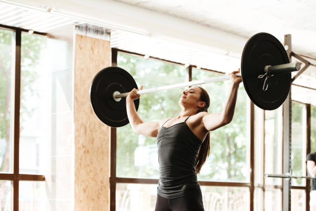 Strong young woman working out with a barbell at the gym