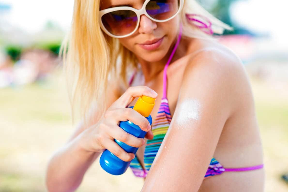 Blond woman in bikini and sunglasses putting on sunscreen
