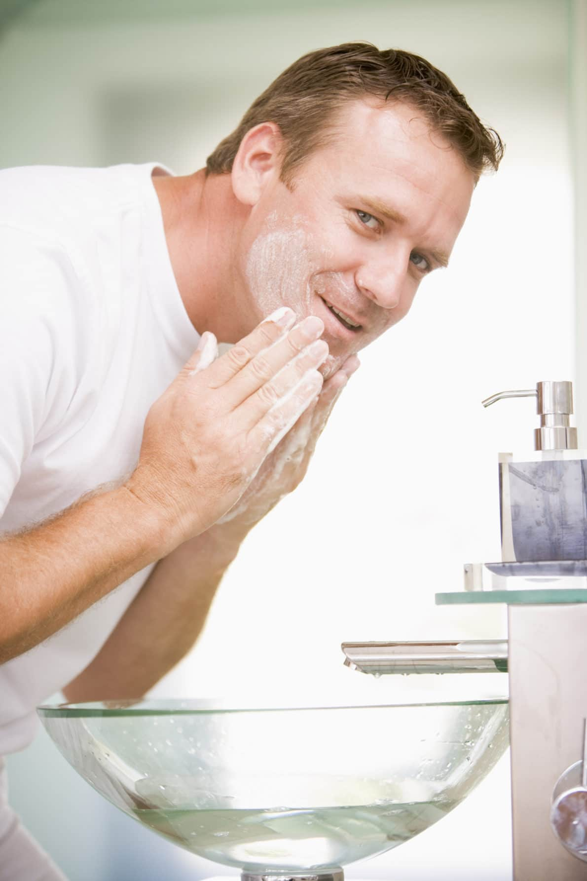 Man in bathroom washing face